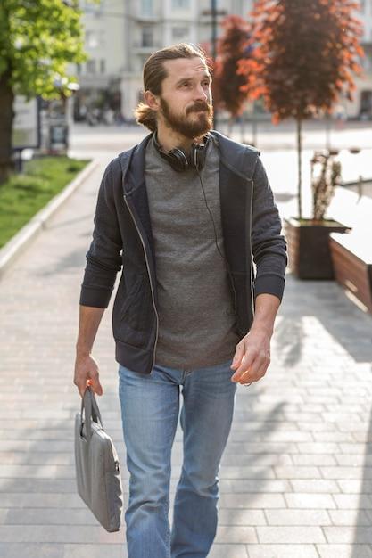 Человек позирует в городе во время ношения наушников Бесплатные Фотографии