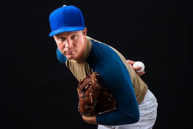 Man posing with baseball glove and ball Free Photo