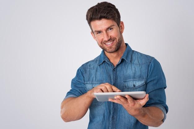 Uomo in posa con camicia di jeans e tablet Foto Gratuite