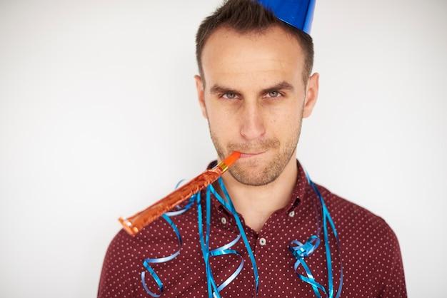 파티 경적 송풍기와 함께 포즈를 취하는 남자 무료 사진