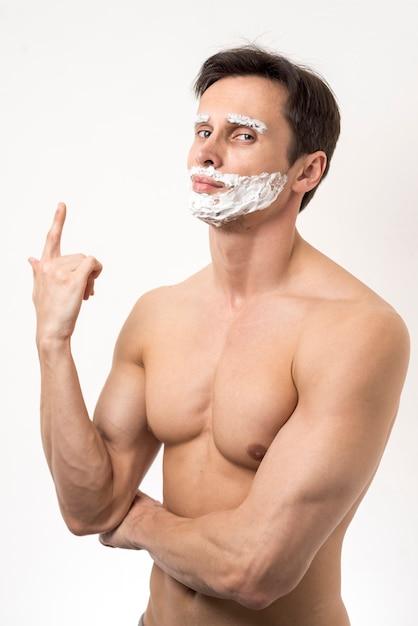 Man posing with shaving foam on face Free Photo