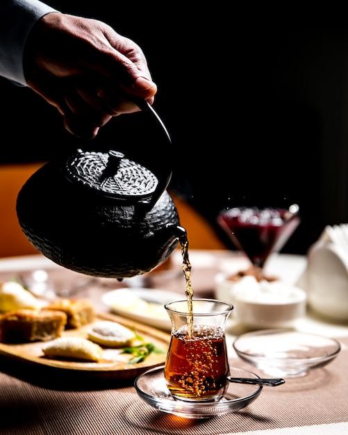 Мужчина наливает черный чай в армуди национальный стеклянный вид сбоку Бесплатные Фотографии