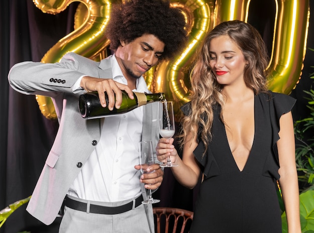 Man pouring champagne in glass held by woman Free Photo
