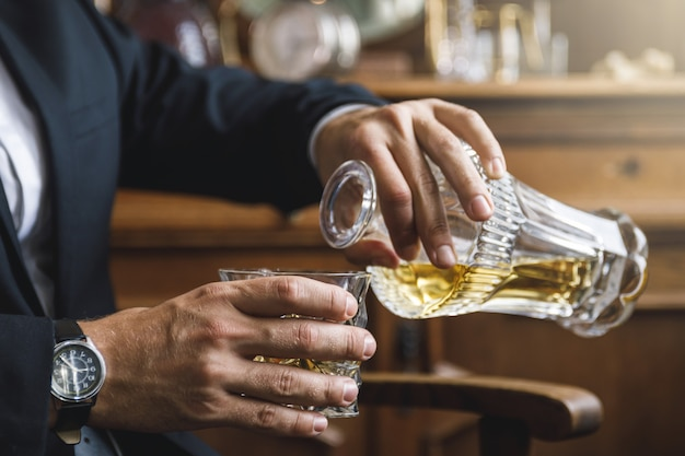 Man pouring expensive whiskey into the crystal drinking glass Premium Photo