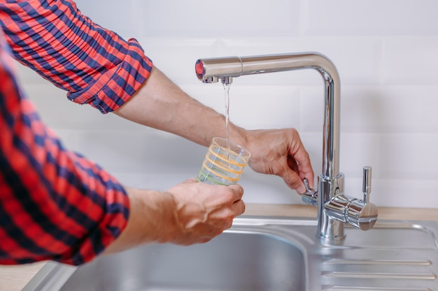 Man pouring glass of water from tap with clean filter in kitchen, close up Premium Photo