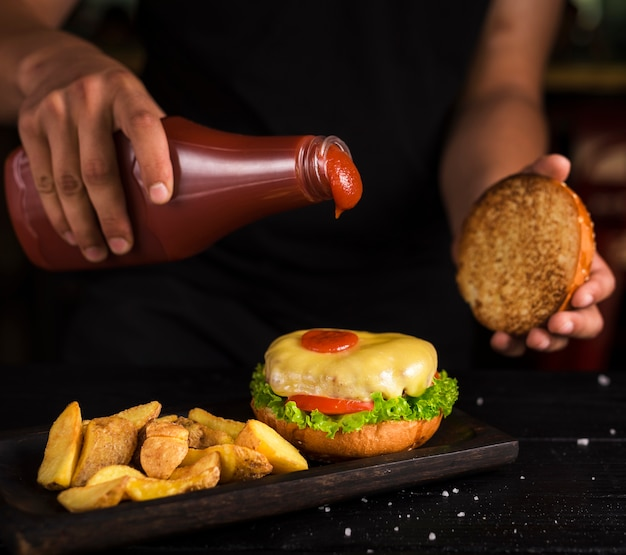 Man pouring ketchup on tasty beef burger Free Photo