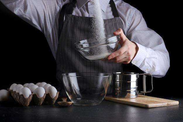 Человек наливает сахар в миску на черном фоне Premium Фотографии