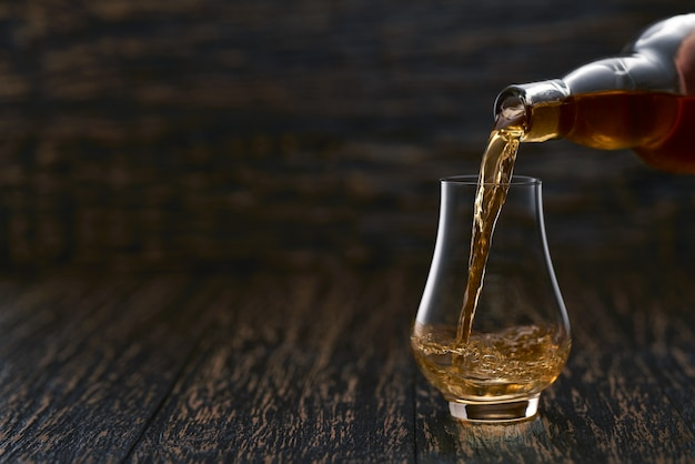 Man pouring whiskey in glass on a wooden table | Premium Photo