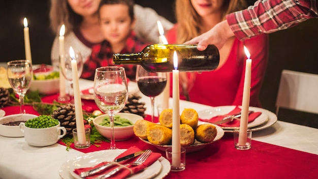 Man pouring winne at christmas dinner Free Photo