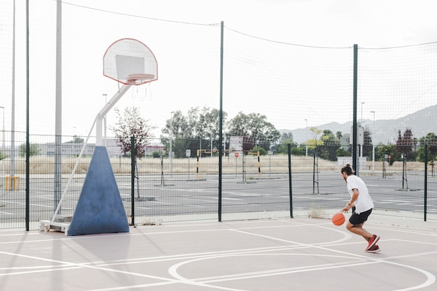 Man practicing basketball near hoop in outdoors court Free Photo