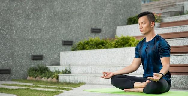 L'uomo a praticare yoga all'aperto con copia spazio Foto Gratuite