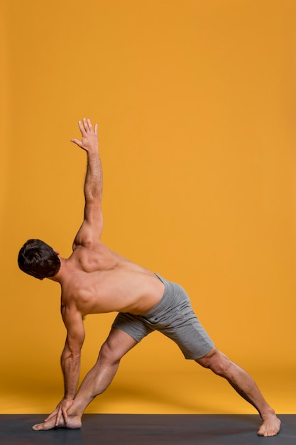 Man practicing in yoga position Free Photo