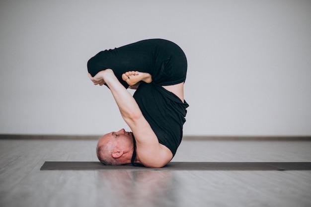 Man practising yoga in the gym Free Photo