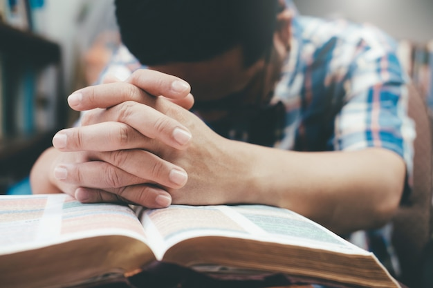 Man praying, hands clasped together on her bible. Premium Photo