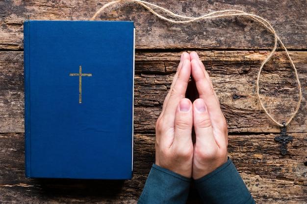 聖書の横に祈って、木製の背景にクロスする男 Premium写真