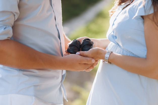 Man and pregnant woman hold shoes for newborn baby in their arms standing on the green field Free Photo