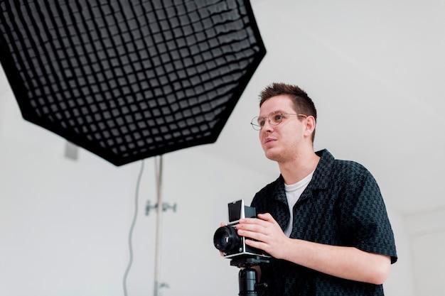 Мужчина готовит студию к съемкам и смотрит в сторону Бесплатные Фотографии