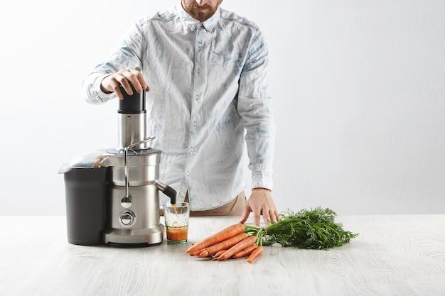 Мужчина выжимает морковь внутри металлической профессиональной соковыжималки, чтобы приготовить вкусный сок на завтрак из свежей моркови, наливаемой в прозрачное стекло. Бесплатные Фотографии