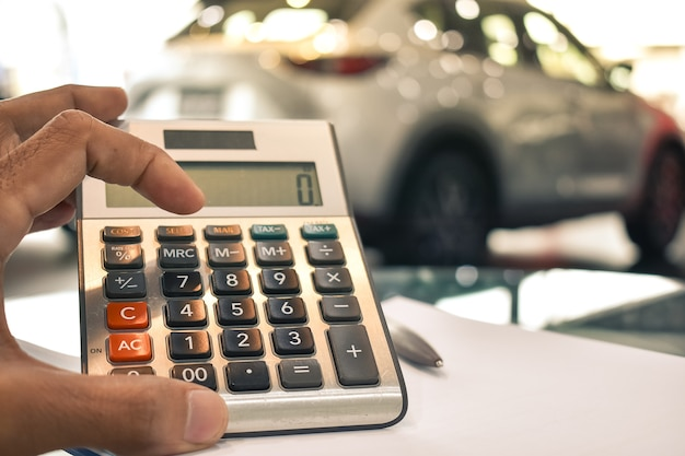 Man Pressing Calculator For Business Finance On Car Showroom Photo