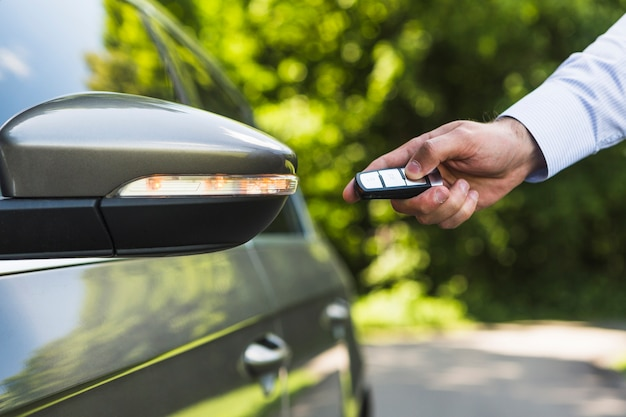 Man pressing remote button to open car door Free Photo