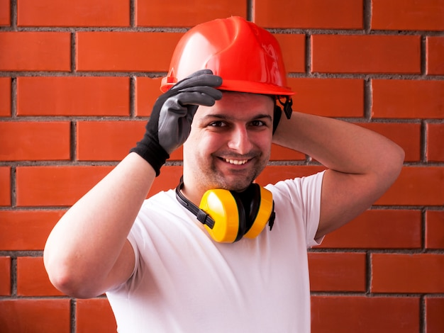 A man in a protective helmet and black gloves against a red brick wall, with noise-reducing headphones around his neck. diy concept and safety. diy do it yourself Premium Photo