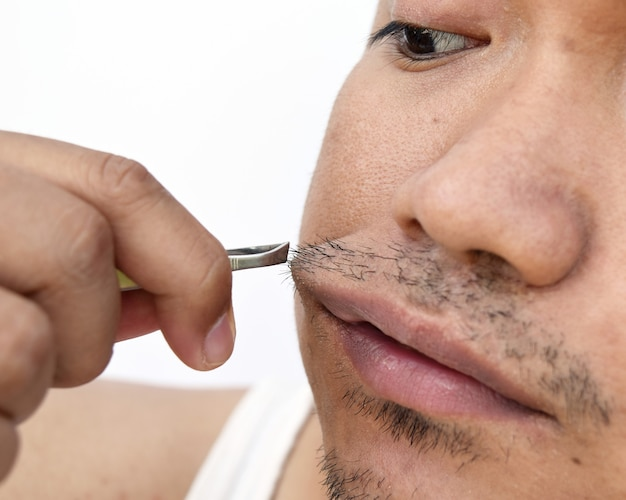 Man pull mustache by tweezers Premium Photo