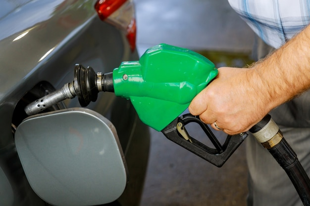 Man pumping gasoline car at gas station being filled with fuel on closeup Premium Photo