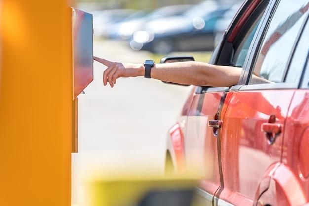 Человек нажимает кнопки парковки на входе в платную парковку Premium Фотографии