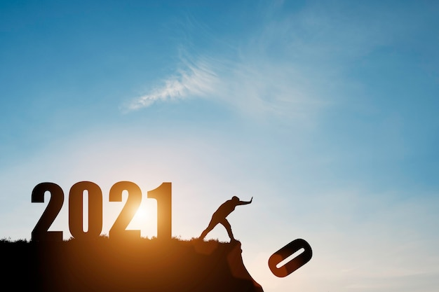 Man push number zero down the cliff where has the number 2021 with blue sky and sunrise. Premium Photo