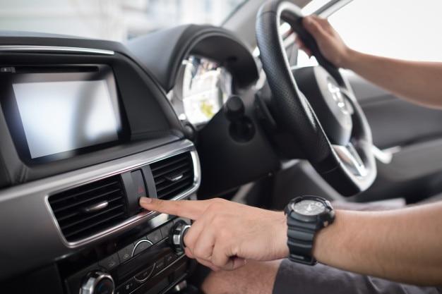 Man pushes a button in the car, modern car interior Premium Photo