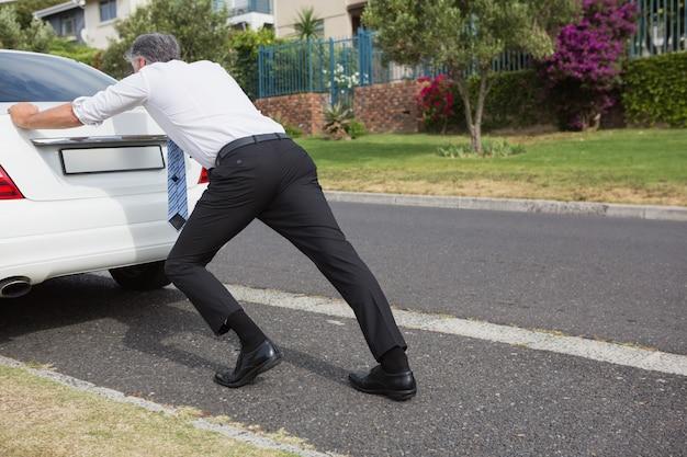 Man pushing his broken down car Premium Photo