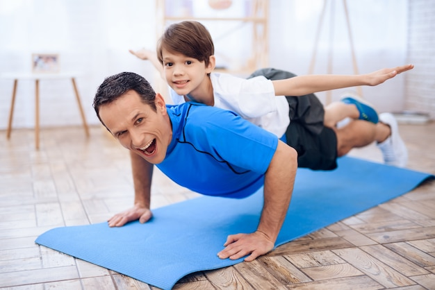 The man pushup from the floor with the boy on his back. Premium Photo