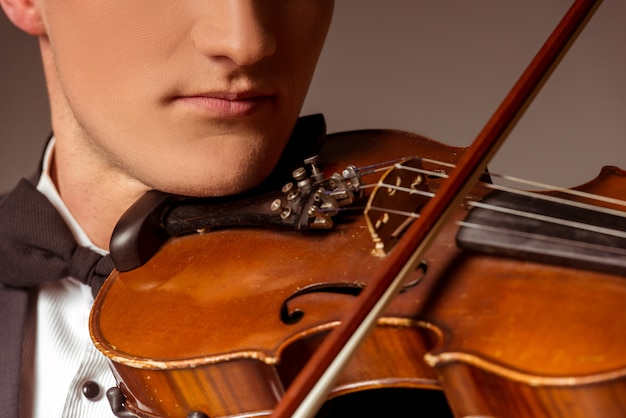 Man put the violin on his neck and plays. Premium Photo