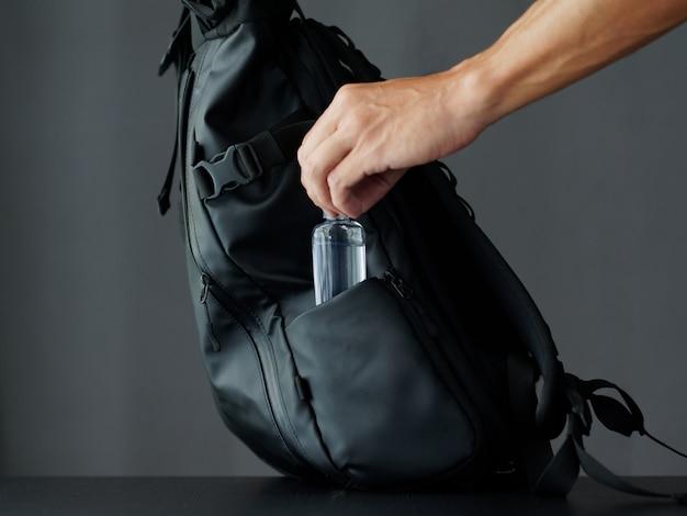 A man puts alcohol gel in a black modern backpack. sanitizer Premium Photo
