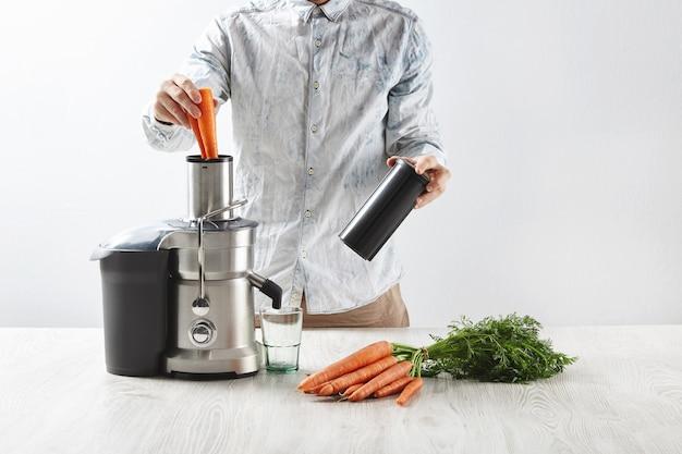Мужчина кладет морковь в металлическую соковыжималку с пустым стаканом, чтобы приготовить вкусный сок на завтрак Бесплатные Фотографии