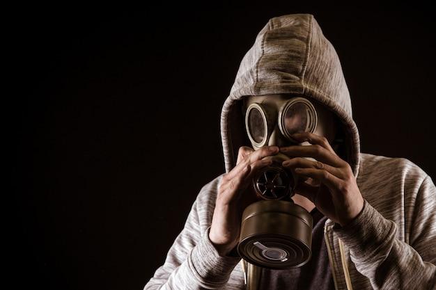 Человек надевает противогаз для защиты от газа. портрет на черном фоне, драматическая раскраска Premium Фотографии