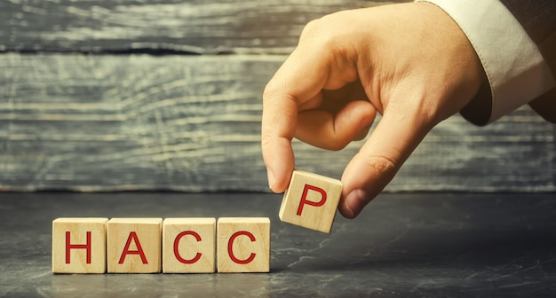 A man puts wooden blocks with the word haccp. Premium Photo