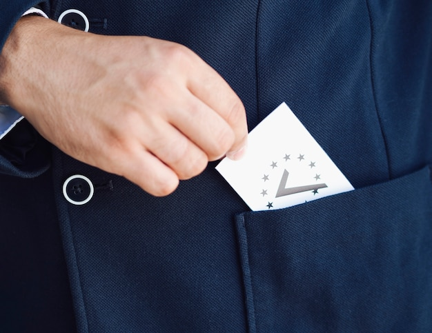 Man putting a ballot in his pocket Free Photo