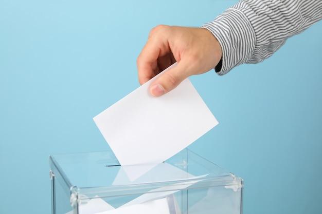 Человек кладет бюллетень в урну для голосования Premium Фотографии