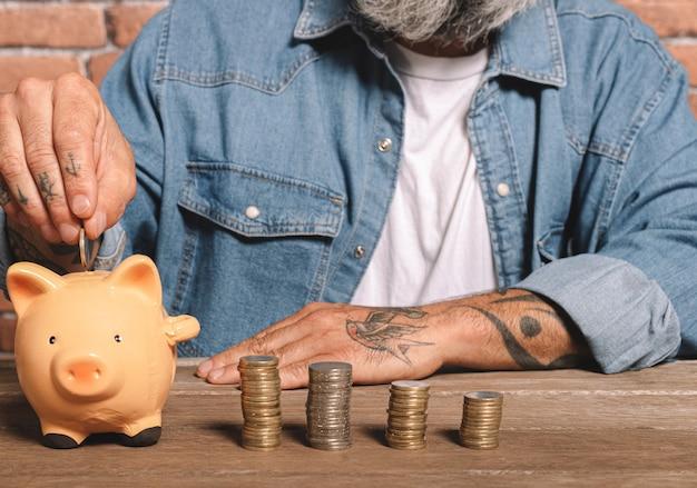お金と金融の概念を節約するためにテーブルにコインのスタックで貯金箱にコインを置く男 Premium写真