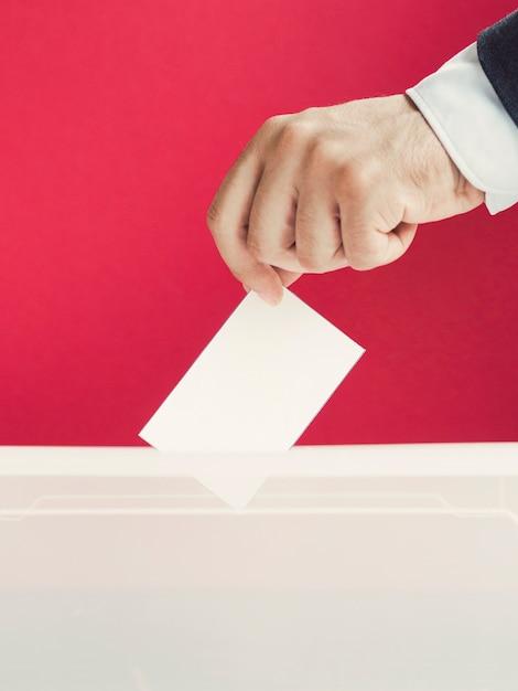Man putting an empty ballot in a box Free Photo