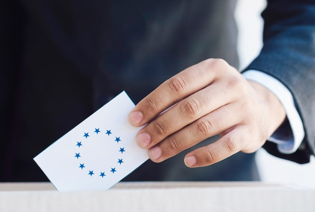 Man putting an european election ballot in a box close-up Free Photo