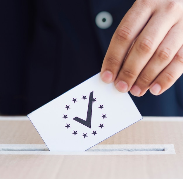 Man putting his ballot in a box close-up Free Photo