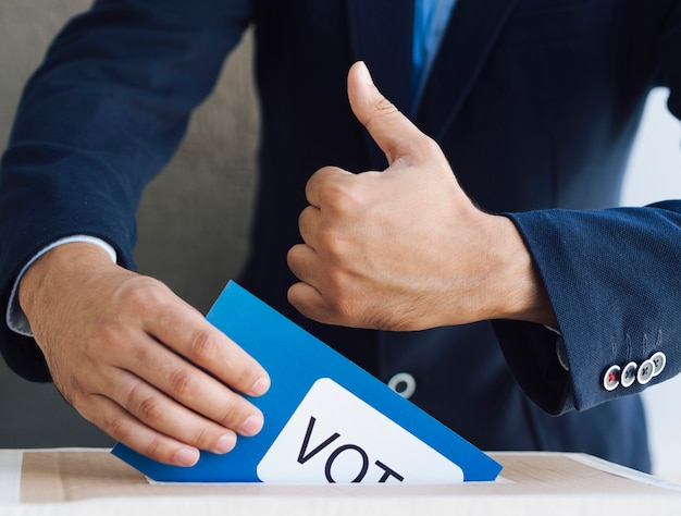 Man putting his ballot in a box Premium Photo