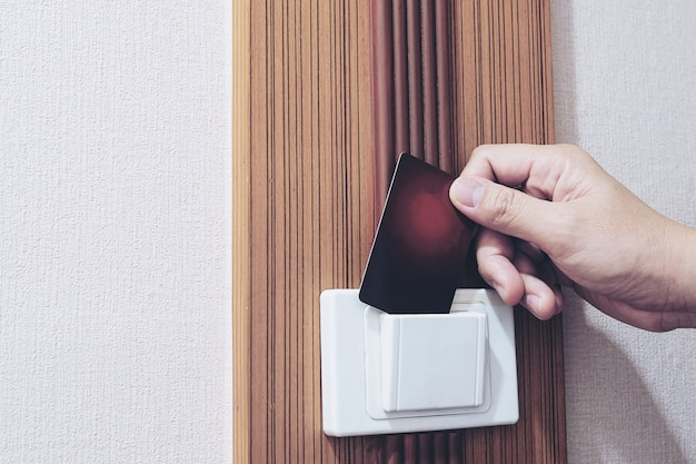 Man putting key card switch in hotel room Free Photo