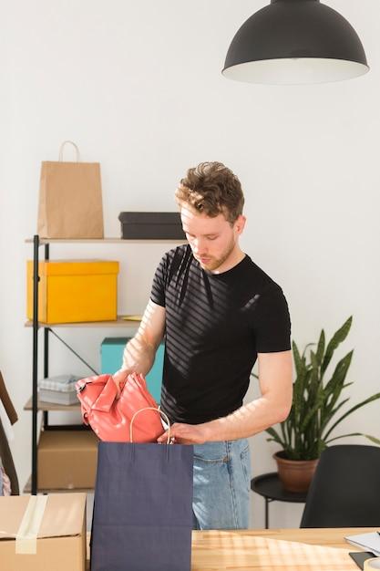 Uomo che mette la camicia in borsa Foto Gratuite