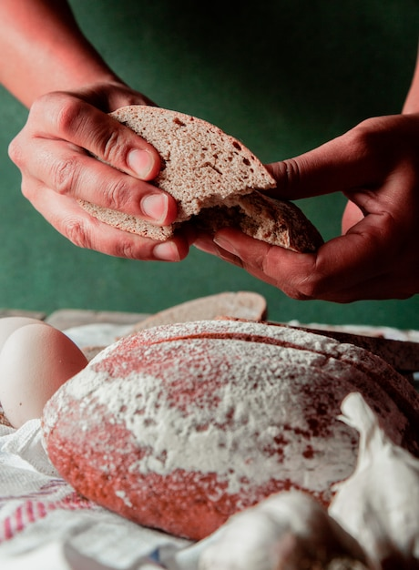 Man putting a slice of black bread in the hand. Free Photo