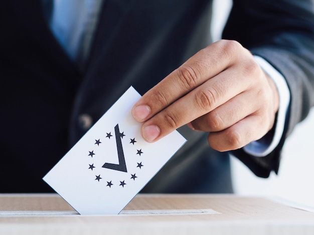 Man putting a verified ballot in a box close-up Premium Photo