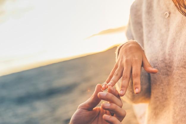 Man putting wedding ring on woman finger Free Photo