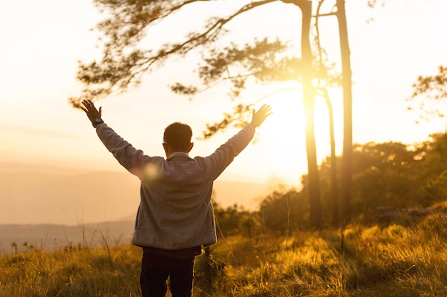 Man raise hand up in the air during sunset on top of mountain Premium Photo